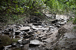 © Licensed to London News Pictures. 04/08/2019. Whaley Bridge, UK. The upstream river that feeds the Toddbrook Reservoir is diverted in to a bywater via a sluice and a dam is increased in height by 1 metre , leaving the riverbed that feeds the reservoir dry . More rain is forecast overnight (Sunday 4th/Monday 5th August) in the town of Whaley Bridge in Derbyshire after earlier heavy rain caused damage to the Toddbrook Reservoir , threatening homes and businesses with flooding. Photo credit: Joel Goodman/LNP