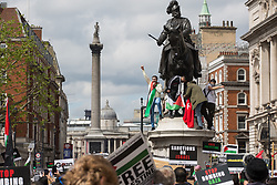 London, UK. 22nd May, 2021. Protesters stand on the plinth of a statue as tens of thousands of people approach Trafalgar Square during the National Demonstration for Palestine. It was organised by pro-Palestinian solidarity groups in protest against Israel's recent attacks on Gaza, its incursions at the Al-Aqsa mosque and its attempts to forcibly displace Palestinian families from the Sheikh Jarrah neighbourhood of East Jerusalem.