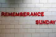 A sign for Remembrance Sunday made of poppies on a breeze block wall inside HMP Bronzefield, a private prison run by Sodexo Justice Services on the outskirts of Ashford in Middlesex, United Kingdom. HMP Bronzefield is an adult and young offender female prison, the only purpose built private prison solely for women in the UK and is the largest female prison in Europe. (photo by Andy Aitchison)