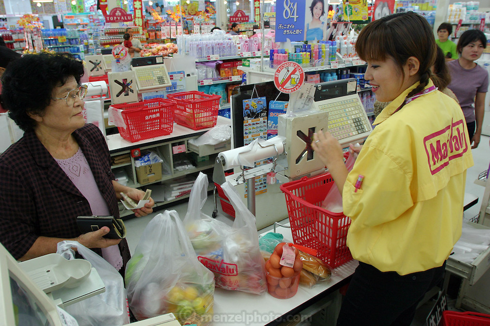 """(KEIKO MATSUDA IS MODEL RELEASED). Grocery store in Yomitan Village, Okinawa, where Keiko Matsuda does some of her shopping. (Supporting image from the project Hungry Planet: What the World Eats.) The Matsuda family of Yomitan Village, Okinawa is one of the thirty families featured, with a weeks' worth of food, in the book Hungry Planet: What the World Eats. Hara hachi bu: """"eat only until 80 percent full,"""" say older Okinawans. The island has been the focus in recent years of researchers trying to discover why a disproportionately large number of Okinawans are living to age 100 or more."""