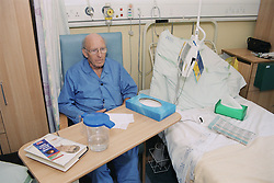 Elderly male patient sitting in chair beside hospital bed on ENT ward waiting to be seen by doctor,