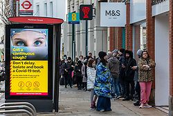 © Licensed to London News Pictures. 27/12/2020. London, UK. Members of the public walk past a Covid-19 information display in Chelsea, South West London as Ministers reveal that the Oxford vaccine could be approved next week and possibly as early as Monday (tomorrow) with a full roll out to start from the 4 January 2021. Last week Health Secretary Matt Hancock announced that yet another new Covid-19 mutation has been discovered in the UK as Downing Street orders many more areas of England to go into Tier 4 lockdown yesterday with tougher new Covid-19 restrictions for many as the mutated strains continue to spread throughout the UK. Photo credit: Alex Lentati/LNP