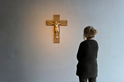 Cologne, Germany, Jan. 2012 - PICTURED: A patron views the Crucifix Rhineland, 2nd half of the 12th century, ivory...Its hard to say what makes more impact: the Kolumba museums vertiginous mix of ancient religious and modern secular artworks, or its astounding, vintage-2007 building from the Pritzker-winning Swiss architect Peter Zumthor. Shift your gaze from an oversize, late-12th-century carved ivory crucifix to a neighboring untitled sculpture by the great Joseph Beuys, then take in the spires of the Cologne Dom cathedral, artfully framed in a nearby floor-to-ceiling window (Kolumbastrasse 4; 49-221-933-193-32; kolumba.de). (Photo © Jock Fistick)