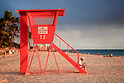 A woman reading a newspaper on a lifeguard stand on Waikiki Beach.