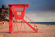 A woman reading a newspaper on a lifeguard stand on Waikiki Beach.