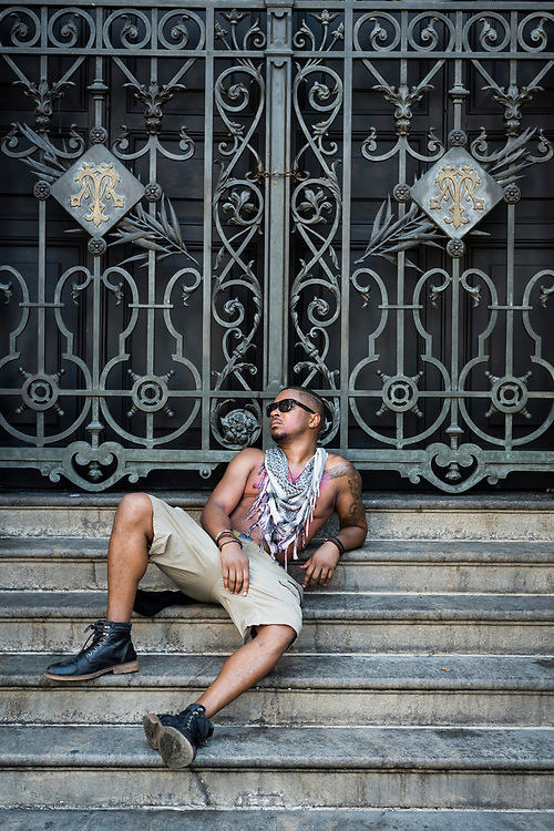 Rio de Janeiro, Brazil - March 10, 2019: Darrien, from the United States and visiting Brazil during Carnival, sits on the steps in front of the Municipal Theater of Rio de Janeiro.