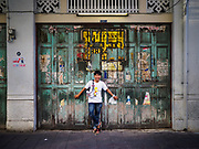 """26 FEBRUARY 2019 - BANGKOK, THAILAND: A man poses for photos against a weathered wall in Bangkok's Chinatown. Bangkok has one of the largest """"Chinatown"""" districts in the world. About 14% of all Thais have some Chinese ancestry and Chinese cultural practices are incorporated in many facets of Thai daily life.       PHOTO BY JACK KURTZ"""