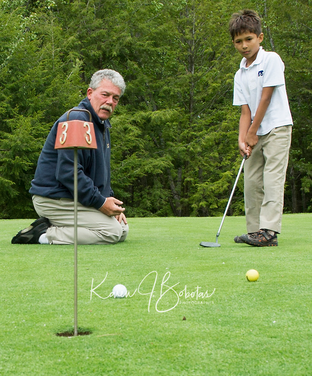Liam Lichocki concentrates on his putt instructed by Randy Annis at Bolduc Park Tuesday evening.  (Karen Bobotas/for the Laconia Daily Sun)