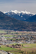 Mount MacFarlane, Crossover Peak, and Mount Slesse (L to R) provide a mountain backdrop to the housing and farmland in the Sardis area of Chilliwack, British Columbia, Canada. Photographed from Hillkeep Regional Park on Chillwack Mountain.