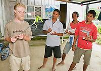 British herpetologist Mark O'Shea holds a Sunda Island pitviper, Cryptelytrops insularis. Looking on are Timorese students Benny Carvalho, Laca Ribeira, and Zito Soares. Bakhita Mission, near Eraulo, Ermera District, Timor-Leste (East Timor)