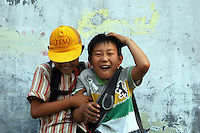 China, Taiyuan, 2008. Yellow hats for safety identify all schoolchildren in Taiyuan. These boys are outside a tiny games shop in a gritty neighborhood near Taiyuan Iron and Steel.