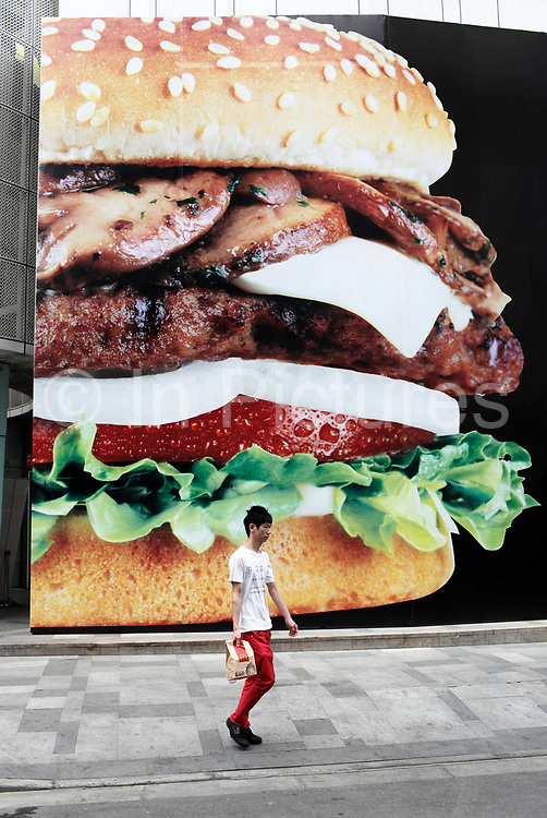 A man carrying a McDonald's takeout bag walks past a large hamburger advertisement in Shanghai, China on 20 May 2010.