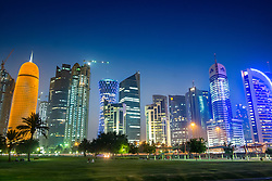 Night view of skyline along Corniche towards modern office towers in Doha Qatar