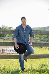 good looking cowboy leaning against a spit rail fence