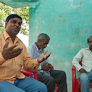 CAPTION: Rammurat Yadav (left), Pradhan (leader) of Baharayen, meets with residents of the village who'd like to set up micro enterprises drawing on electricity generated under the SPEED initiative. LOCATION: Baharayen, Faizabad District, Uttar Pradesh, India. INDIVIDUAL(S) PHOTOGRAPHED: From left to right - Rammurat Yadav, Ram Khilavan and unknown.