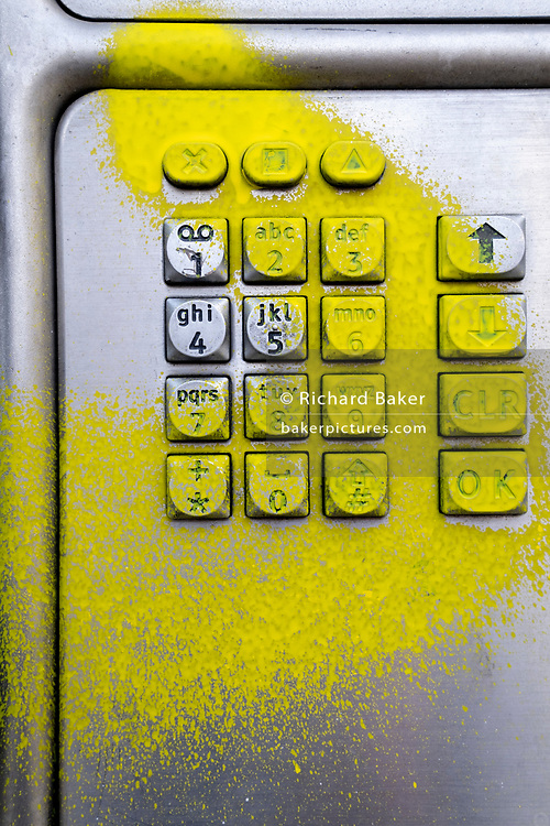 A detail of a public BT landline phone kiosk has been vandalised by the spraying of yellow aerosol paint over its keypad on the Southbank in Waterloo, on 11th March 2021, in London, England.