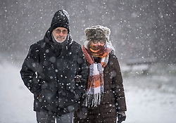 © Licensed to London News Pictures. 24/01/2021. London, UK. An elderly couple walk in heavy Snowfall on Hampstead Heath in Hampstead in north London. Parts of the UK continue to suffer from flooding caused by Storm Christoph. Photo credit: Ben Cawthra/LNP