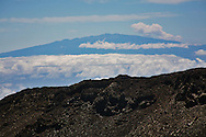 The rocky 10,000 ft. summit of Mt. Haleakala, House of the Sun, on Maui. .Mt. Haleakala is considered to be a semi-dormant volcano and features a 7 mile wide crater. .Mauna Kea, located on the island of Hawaii, is seen in the background.