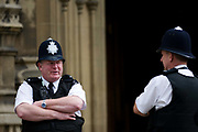 Two Metropolitan police officers talk on duty while guarding Britain's parliament in Westminster, London. Standing beneath the main members' entrance of the Gothic tower, the two policemen talk outside the Palace of Westminster where the British Government meets and weilds its poeer. The Palace, also known as the Houses of Parliament or Westminster Palace, is where the two Houses of the Parliament of the United Kingdom (the House of Lords and the House of Commons) conduct their business. It is therefore a potent symbol for British Governmental power.