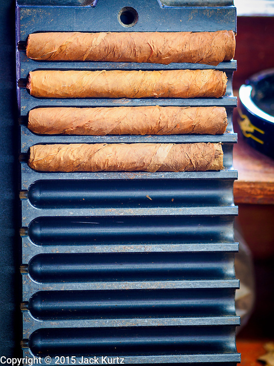 30 APRIL 2015 - TAMPA, FLORIDA, USA: Hand rolled cigars in a press at Tabanero Cigars, a cigar factory and coffee house in the Ybor City section of Tampa, FL. Tabanero Cigars handrolls cigars in the traditional Cuban style. Most of the rollers at Tabanero have immigrated to the US from Cuba. Ybor is a historically Cuban immigrant community that has been redeveloped and gentrified into a popular tourist destination lined with cigar factories, boutiques and cafes.     PHOTO BY JACK KURTZ