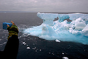 A Sea Shepherd crew member snaps a photo of a passing iceberg in the Southern Ocean. (Photo by Adam Lau)