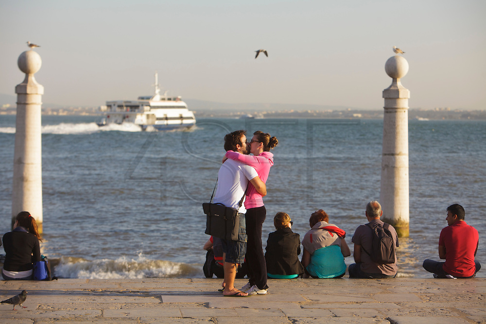 People enjoying sunset at Cais das Colunas (Columns Pier)  by the Tagus riverside. The pier is part of Terreiro do Paço, the largest Lisbon square, and is one of the most well-know place to visit in Lisbon.