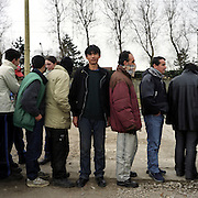 Refugees queuing for food in Calais, France. The food is being given out by the Secour Cathlique charity. .After the Sangatte refugee camp closed down an average of 200 refugees lived on the streets of Calais, without food, money or accommodation, trying most nights to get to Britain.  There were many different nationalities, mainly Iraqi and Afghani, but also Sudanese, Palestinian and Turkish. 95% are male, aged between 16 and 50.