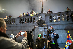 © Licensed to London News Pictures . 05/11/2019. London, UK. A mask is placed on a bust of John Jellicoe, 1st Earl Jellicoe in Trafalgar Square and a Free Assange poster is held up . Supporters of Anonymous , many wearing Guy Fawkes masks , attend the Million Mask March bonfire night demonstration , in Trafalgar Square in central London . Photo credit: Joel Goodman/LNP