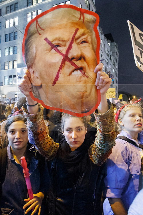 © Licensed to London News Pictures. 09/11/2016. New York, USA. Thousands of anti-Trump demonstrators protest outside Trump Tower after marching from Union Square in New York City, on Wednesday, 9 November 2016 following the presidential election won by Donald Trump. Photo credit: Tolga Akmen/LNP