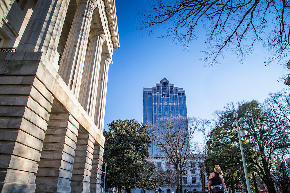 woman walks past North Carolina State Capitol towards Fayetteville Street and the Wells Fargo Building in Raleigh, NC.
