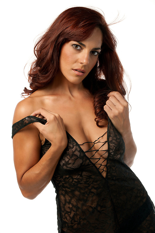 Young hispanic woman in lingerie undressing and looking sensual at camera.