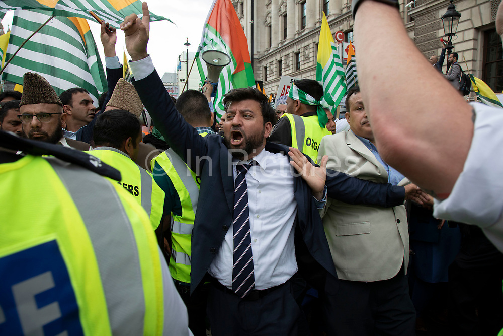 Demonstration to free Kashmir is shepherded by a large number of police with their arms linked to prevent the crowd from surging in Westminster on 3rd September 2019 in London, United Kingdom. Kashmiris waving flags gathered in Westminster and marched along Whitehall in protest at Indian Prime Minister Narendra Modi's removal of the special autonomous region rights of Kashmir.