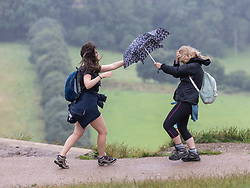 Licensed to London News Pictures. 30/07/2021.Dorking, UK. Hikers, left, Sarah Done 24 and Catherine Edwards enjoy a climb up Box Hill in Surrey despite the unseasonal stormy conditions today. Storm Evert hit the South Coast of England this morning with winds speed in excess of 65mph as the Met Office issue weather warnings for high winds, coastal gales and heavy rain with disruption to travel. Photo credit: Alex Lentati/LNP