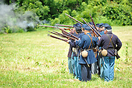 Old Bethpage, New York, USA - July 21, 2012: Troops firing muskets at Camp Scott, a Union Army training camp, as portrayed by Federal Re-enactors at Old Bethpage Village Restoration, to commemorate 150th Anniversary of American Civil War.
