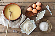 Overhead shot of table with ingredients and bowl with custard cream: fresh eggs, milk, flour and sugar.