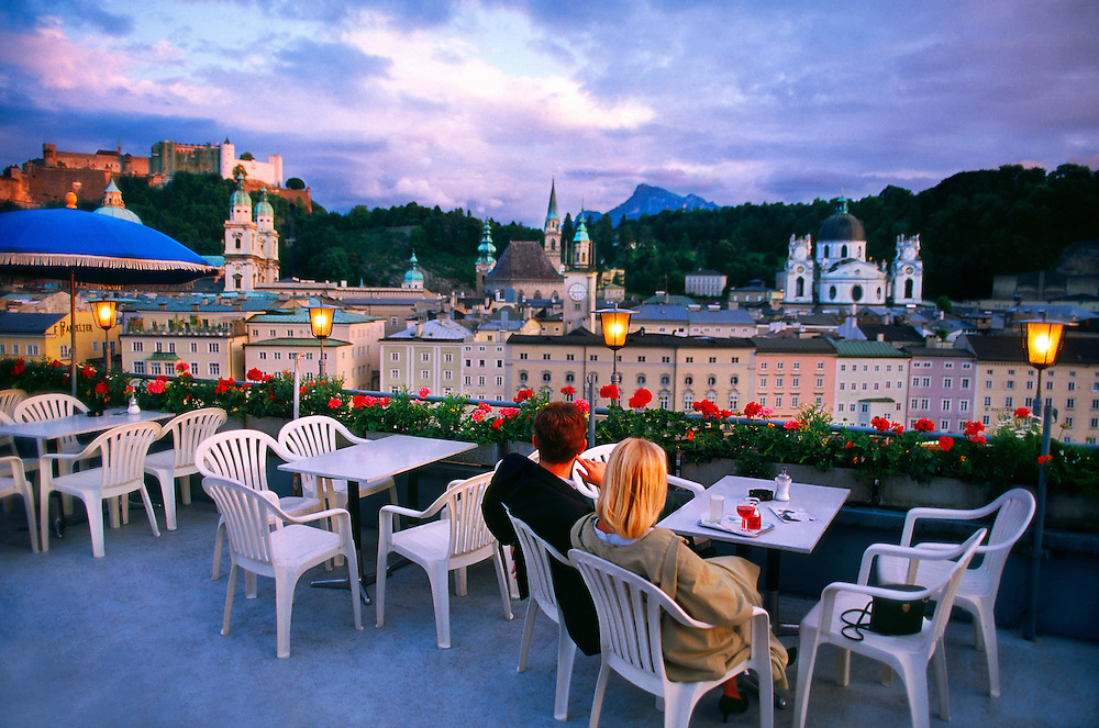 Couple enjoying a drink at the cafe atop the Hotel Stein overlooking the Old Town, Salzburg, Austria.