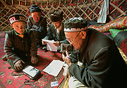 """Abdul Rashid Khan listen to tapes and read letters that we brought him from his cousin Abdul Haleem, exiled in turkey since 1982. Kara Jelgha (""""black valley"""") summer camp. The campment of Abdul Rashid Khan, the king of the Kyrgyz.<br /> <br /> Adventure through the Afghan Pamir mountains, among the Afghan Kyrgyz and into Pakistan's Karakoram mountains. July/August 2005. Afghanistan / Pakistan."""