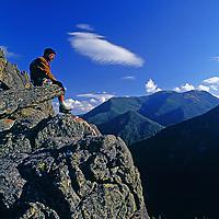 A rock climber overlooks Gallatin Canyon and Madison Range near Big Sky.