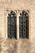 Building exterior medieval church architectural feature decorated glass window in stone wall with metal grid, Inglesham, Wiltshire, England, UK
