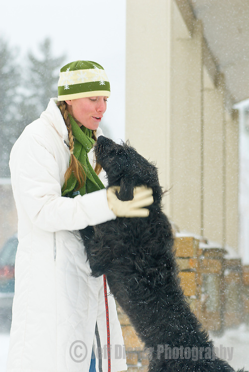A young woman plays with her dog on a wintry day in Jackson, Wyoming.