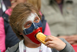 A Russia fan eats a snack in the stands