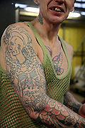 A prisoner shows off his tattoos in the engineering workshop of Coldingley prison..HMP Coldingley, Surrey was built in 1969 and is a Category C training prison. Coldingley is focused on the resettlement of prisoners and all prisoners must work a full working week within the prison. Its capacity is 390 prisoners.