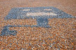 Alien design in pebbles on Brighton beach