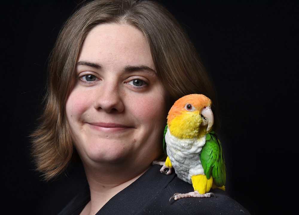 """Photo by Mara Lavitt -- Special to the Hartford Courant<br /> March 21, 2015, Middletown<br /> The eighth FeatherFest was held in Middletown by the Connecticut Parrot Society providing visitors with education about parrots and other birds. Jessica El-Beck of Meriden with her white-bellied caique named Zeke. El-Beck adopted Zeke through the CT Parrot Society's adoption program. """"I have a tattoo of Zeke on my leg. He's holding a banner that says 'Adopt'""""."""