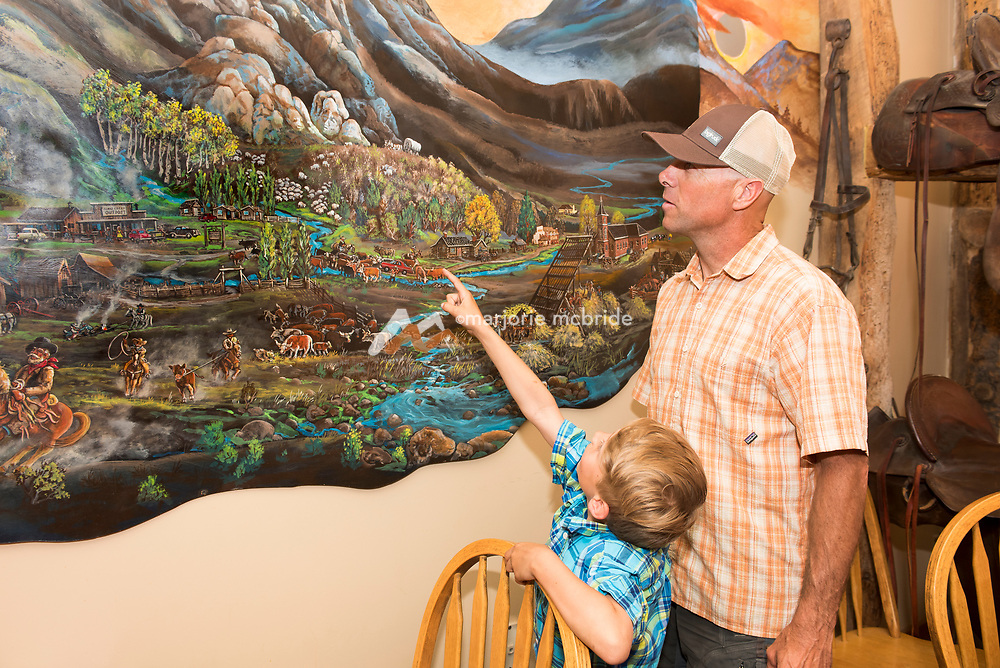 Father and son look at mural painting on wall while enjoying dinner at Almo Outpost Steak House restaurant in Southern Idaho. MR