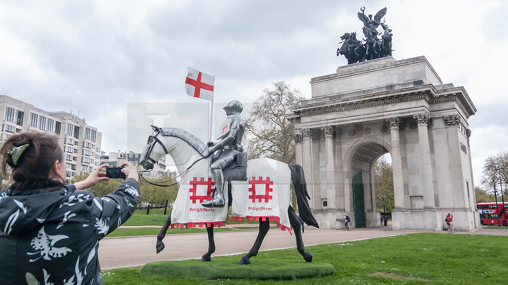 © Licensed to London News Pictures. 22/04/2015. Wellington Arch, London. A tourist takes a photo as English Heritage unveil a 15ft St George at Wellington Arch in honour of the Patron Saint ahead of England's largest St George's Day celebration at Wrest Park as well as the launch of a nationwide tour which will see the knight open jousting tournaments at castles across England. Photo credit : Stephen Chung/LNP