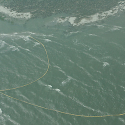 Oil containment booms are displaced by heavy surf away from the marshlands they are designed to protect near the coast of Breton Sound in the Gulf of Mexico off the coast of Louisiana, U.S., on Saturday, May 1, 2010. The BP Plc Deepwater Horizon drilling rig oil spill is threatening the Breton Sound islands that are a habitat for the Louisiana state bird the brown pelican. Photographer: Derick E. Hingle.