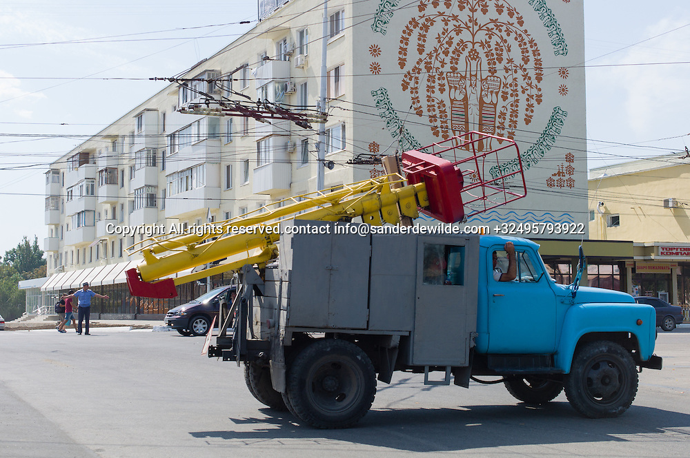 20150826 Tiraspol, Transnistria,   Moldova. A vehicle passes by in the 25th of October street while a policeman organises traffic and a large Moldovan painting shows on the side of this appartment building
