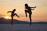Two nude women leaping for the sky at sunset at the Bonneville Salt Flats, Utah
