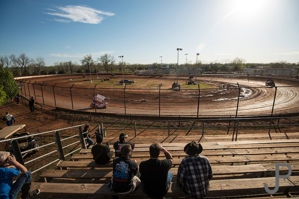 Fans watch from the stands as the cars race around the dirt track.